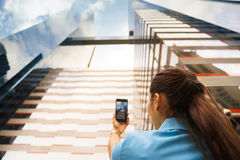 Foto do tiro da pessoa do prédio de escritórios com telefone Fotografia de Stock Royalty Free
