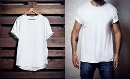Foto do tshirt branco que pendura no fundo de madeira e no homem farpado que vestem o Tshirt claro Modelo vazio vertical Imagem de Stock Royalty Free