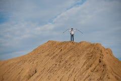Foto do turista masculino de longe com mãos acima com as varas para andar no monte Fotos de Stock Royalty Free