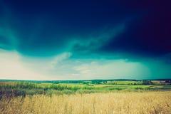 Foto do vintage de nuvens de tempestade sobre o campo de trigo Foto de Stock