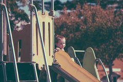Foto do vintage do menino da criança na corrediça no campo de jogos Imagem de Stock Royalty Free