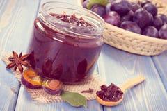 Foto do vintage, doce de fruta fresco da ameixa no frasco, especiarias e frutos maduros na cesta de vime, sobremesa doce saudável Fotografia de Stock