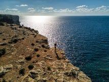 Foto do zangão - uma mulher sobre os penhascos da ilha de Comino, Malta foto de stock