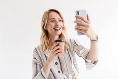 Foto dos vidros vestindo de sorriso da mulher atrativa que tomam a foto do selfie e que guardam o copo de papel foto de stock royalty free