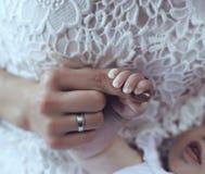 Foto dulce de la mano linda del bebé en manos de la mamá foto de archivo