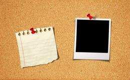 Foto e blocchetto per appunti in bianco sulla scheda del sughero Immagine Stock