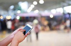 Foto e smartphone borrados na feira profissional e na uma compra de parada Fotos de Stock Royalty Free