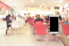 Foto e smartphone borrados no centro do alimento no shopping e Imagem de Stock