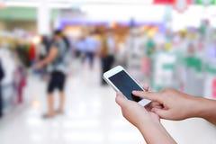 Foto e smartphone borrados no fundo do shopping Imagem de Stock Royalty Free