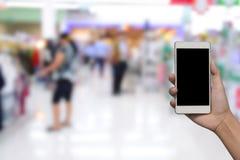 Foto e smartphone borrados no fundo do shopping Fotos de Stock Royalty Free