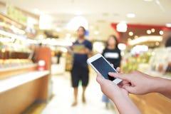 Foto e smartphone borrados no fundo do shopping com BO Imagem de Stock Royalty Free