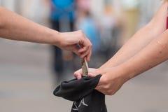 Foto einer Hand, die Almosen zum Hut gibt stockfotografie