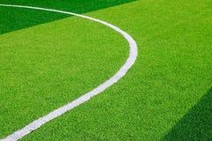 Foto eines grünen synthetischen Grassportfeldes mit der weißen Linie SH Lizenzfreie Stockbilder