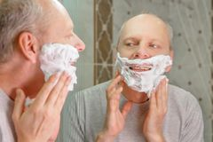 Foto eines Mannes, der sein Gesicht rasiert lizenzfreies stockbild