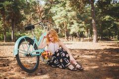 Foto eines schönen rothaarigen Mädchens in einem Herbstwald mit Blumen Mädchen mit einem Fahrrad im Wald stockfoto