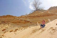 Foto eingelassener Sommer Ein Mädchen in der Wüste lässt das Sand throug lizenzfreie stockbilder