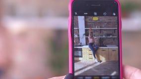 Foto en el teléfono móvil, mujer divertida joven que presenta para la fotografía en cierre del smartphone para arriba en cocina metrajes