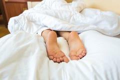 Foto en la cama de los pies de las muchachas que mienten en la almohada Fotos de archivo libres de regalías