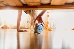 Foto entonada de la muchacha enfadada que alcanza para el despertador debajo del b Fotografía de archivo libre de regalías