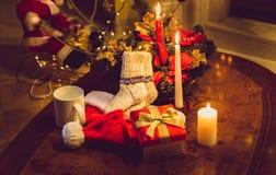 Foto entonada de las velas de la Navidad, del giftbox abierto y de los calcetines de lana Imágenes de archivo libres de regalías