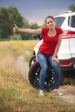 Foto entonada del coche roto wirh de la mujer joven witting en la rueda de repuesto e hitch0hiking imagen de archivo libre de regalías