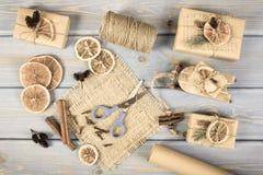 Foto envejecida, accesorios, decoración y regalos envueltos para la Navidad con el trineo de madera en viejos tableros Fotografía de archivo