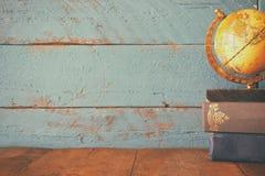 Foto för bästa sikt av tappningjordklotet och bunt av böcker på träskrivbordet tappning filtrerad bild arkivbild