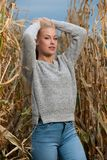 Foto för bloggstilmode av den gulliga blonda kvinnan på havrefält i sen höst royaltyfri bild