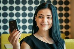 Foto för brunettdanandeselfie genom att använda en smartphone Arkivbild