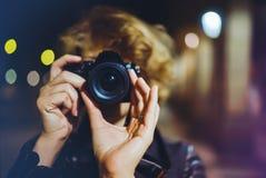 Foto för danande för Hipsterfotvandrare som turist- rymmer i handkamera på bakgrund av den atmosfäriska staden för afton, blogger arkivfoton