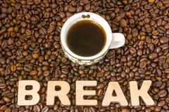 Foto för kaffeavbrott Koppen med bryggat kaffe är på tabellen, som fyllde med grillade kaffebönor, bredvid ordavbrott Idé att pla arkivfoto