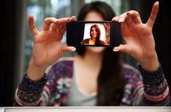 Foto för kvinnadanandesjälv med smartphonen Royaltyfri Bild