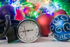Foto för medicinsk jul och för nytt år - blodtryckmåttet eller sphygmomanometeren lokaliseras nära bollar för julgran i blurr Arkivbild