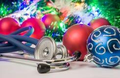 Foto för medicinsk jul och för nytt år - stetoskopet eller phonendoscope lokaliseras nära bollar för julgran i oskarp bakgrund Arkivbild