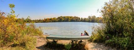 Foto för panoramaformatlandskap av en bänk som förbiser en sjö med 2 personer som ser vattnet Härlig kanadensare arkivfoto