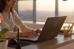 Foto för sidosikt av en kvinnlig programmerare som använder bärbara datorn, arbete, maskinskrivning som surfar internet på arbets Royaltyfria Bilder