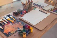 Foto för sidosikt av en palett med penseldrag och målarpenslar Den färgrika gouachen, färgpennor ställer in på målarearbetsplatse Royaltyfri Foto