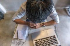 Foto för sikt för hög vinkel av den asiatiska mannen som arbetar på bärbara datorn arkivfoto
