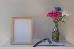 Foto-Feld auf einem hölzernen und Blumen im Glas, Buch auf weißem Hintergrund Stockbild