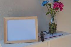 Foto-Feld auf einem hölzernen und Blumen im Glas, Buch auf weißem Hintergrund Lizenzfreie Stockfotos