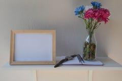 Foto-Feld auf einem hölzernen und Blumen im Glas, Buch auf weißem Hintergrund Stockfotos
