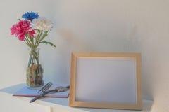 Foto-Feld auf einem hölzernen und Blumen im Glas, Buch auf weißem Hintergrund Stockbilder