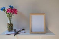 Foto-Feld auf einem hölzernen und Blumen im Glas, Buch auf weißem Hintergrund Lizenzfreies Stockfoto