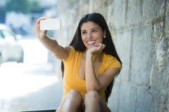 Foto feliz sonriente del selfie del autorretrato de la mujer que toma latina atractiva y dulce con el teléfono móvil Fotografía de archivo libre de regalías
