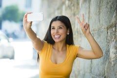 Foto feliz sonriente del selfie del autorretrato de la mujer que toma latina atractiva y dulce con el teléfono móvil Imagen de archivo libre de regalías
