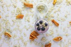 Foto från ovannämnt av en handgjord blåbäryoghurt som dekoreras med den torkade mango och mandlar i en exponeringsglaskrus med vi arkivbild