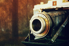 Foto för dubbel exponering och abstrakt begreppav den gamla tappningkameralinsen över trätabellen Selektivt fokusera Royaltyfria Bilder