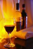 Foto-fyllt genomskinligt exponeringsglas för rött vinexponeringsglas på bakgrunden av två fulla flaskor av rött och vitt vin Royaltyfria Bilder