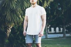 Foto Gebaarde Spiermens die Witte Lege t-shirt en borrels in de zomertijd dragen De groene vage Achtergrond van de Stadstuin, Royalty-vrije Stock Afbeeldingen