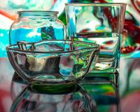 Glass of water with drop and colored background royalty free stock photos